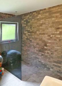 Auschnitt einer offenen Dusche, mit einer gläsernen Trennwand, neu gefliest, ein Handwerker verrichtet am Boden noch letzte Arbeiten
