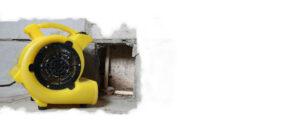 Professionelle Gebäudetrocknung nach Wasserschaden. Gelbes Trocknungsgerät steht vor einem Mauerausschnitt.