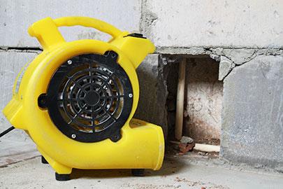 Professionelle Bautrocknung nach Wasserschaden. Gelbes Trocknungsgerät steht vor einem Mauerausschnitt.