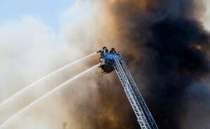 Zwei Feuerwehrmänner auf einer ausfahrbaren Leiter, umhüllt von dunklem Rauch spritzen Wasser aus Schläuchen
