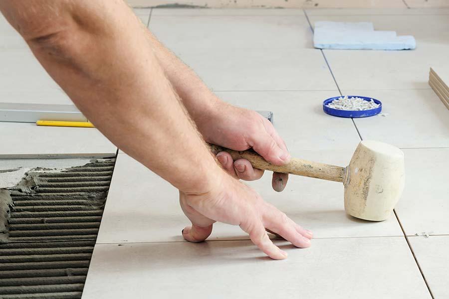 Fliesenlegen: Bildausschnitt von hellen Fliesen am Boden während zwei Männerhände noch am Fliesen sind