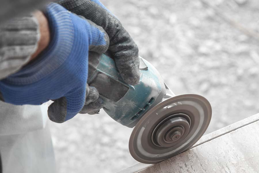 Fliesenlegen: Ausschnitt einer Hand mit Handschuhen, die eine Kreissäge hält und Fliesen schneidet.