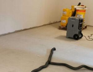 leerer Raum mit schwarzen Schläuchen die in den Boden gehen und großen Trocknungsgeräten sind zu sehen