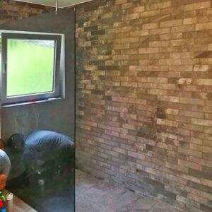 Auschnitt einer offenen Dusche, mit einer gläsernen Trennwand, neu gefliest, während ein Handwerker noch am Boden letzte Arbeiten verrichtet