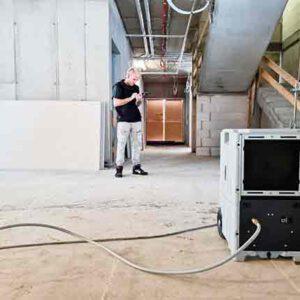 rechts im Foto steht ein großes rechteckiges Bautcknungsgerät innerhalb eines großen, leeren Gebäudekomplexes Mittig steht ein junger Mann in heller Hose, chwarzem T-Shirt, mit auffälliger blonder Kurzhaarfrisur der auf einem Handy tippt