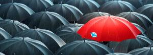 Viele schwarze Regenschirme, von oben betrachtet, nur einer ist rot und hat den Phönix-Vogel als Logo aufgedruckt
