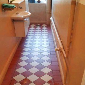 Ausschnitt eines neu gefliesten Badezimmer Bodens, mit rot-weißen Fliesen im Karo-Design
