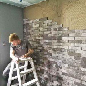 Badezimmer wird gefliest, kleine rechteckige Kacheln sind zur Hälfte bereits an der Wand angebracht, Handwerker steht auf der Leiter