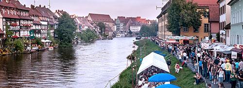 Menüpunkt Kontakt. Ansicht auf Bamberg am Kanal, es sind Menschenmassen, Fahrgeschäfte und Kirchweihbuden auf der rechten Bildhälfte zu sehen, mittig der Fluß und links eine Häuserfront die an Klein Venedig erinnert zu sehen