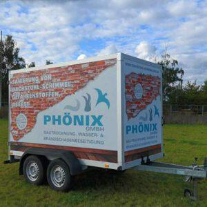 Phönix-Bautrocknung-Anhänger mit auffälliger Folierung: eine weiße Wand, zur Hälfte sind rote Backsteine sichtbar, darauf ein großer Schriftzug bezüglich Schimmelsanierung und das Phönix Logo