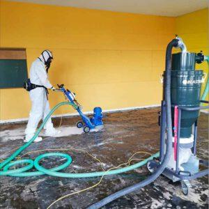 Mann kompletten Schutzanzug und Atemmaske schäumt einen Boden ein in einem großen, leeren Raum