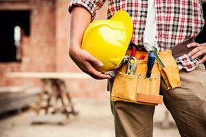 Unser Schadenservice. Ausschnitt eines Handwerkers mit Handwerksgürtel und Schutzhelm in der Hand, im unscharfen Hintergrund sind Holzbretter und eine Baustelle zu erkennen