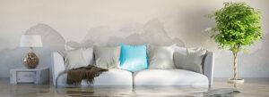 Wohnzimmer, zu sehen eine helle Couch mit blauem Kissen, links und rechts der Couch stehen ein Schränkchen mit Lampe darauf und eine hoch gewachsene Grünpflanze, der Boden des Zimmers steht bis zur Hälfte der Couch unter Wasser, an der Wand sind großflächige Wasserflecken zu sehen